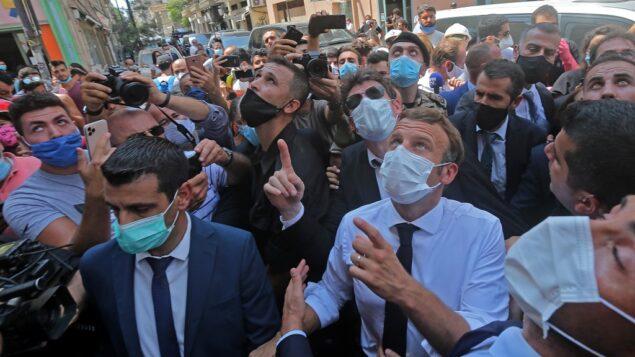 الرئيس الفرنسي إيمانويل ماكرون يتحدث مع الناس أثناء زيارته لحي الجميزة في بيروت، الذي لحقت به أضرار جسيمة بسبب انفجار ضخم في العاصمة اللبنانية، 6 أغسطس 2020. (AFP)