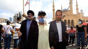 رجل يقف لالتقاط صورة مع مجسمات لحسن نصر الله (يسار)، زعيم حزب الله، ووزير الخارجية اللبناني السابق جبران باسيل، شنقها متظاهرون في وسط بيروت، 8 أغسطس 2020 (AFP)