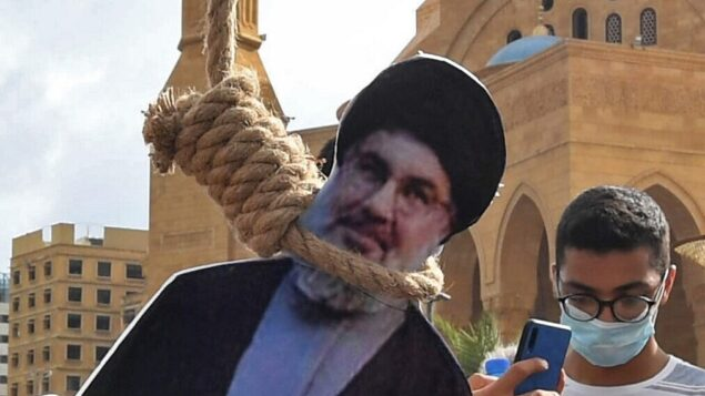 مجسم لحسن نصر الله، زعيم تنظيم حزب الله اللبناني، معلق بحبل مشنقة من قبل متظاهرين لبنانيين في وسط بيروت، خلال مظاهرة ضد القيادة السياسية، 8 أغسطس 2020 (AFP)