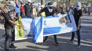 شباب فلسطينيون يحملون صورة لولي عهد أبوظبي الشيخ محمد بن زايد آل نهيان خلال احتجاج على قرار الإمارات العربية المتحدة تطبيع العلاقات مع إسرائيل، في قرية ترمسعيا بالقرب من مدينة رام الله بالضفة الغربية، 19 أغسطس، 2020. (JAAFAR ASHTIYEH / AFP)