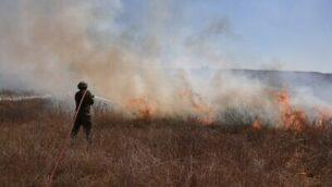 جندي إسرائيلي يطفئ حريقا ناجما عن إطلاق بالونات حارقة من القطاع الفلسطيني في حقل قريب من كيبوتس نيرعم الجنوبي، بالقرب من الحدود مع قطاع غزة ، 25 أغسطس.  (Menahem KAHANA / AFP)