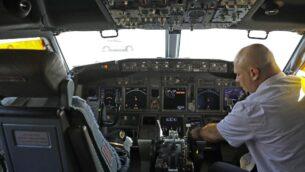 أحد أفراد الطاقم يجلس ا في قمرة القيادة لطائرة 'إل عال'، قبل انطلاق أول رحلة تجارية على الإطلاق من إسرائيل إلى الإمارات العربية المتحدة في مطار بن غوريون بالقرب من تل أبيب والتي ستنقل وفدا أميركيا إسرائيليا إلى الإمارات بعد الإعلا عن اتفاق التطبيع، 31 أغسطس، 2020. (NIR ELIAS / POOL / AFP)