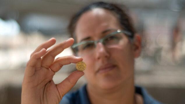 لآيات نداف-زيف، مديرة عمليات التنقيب الأثري تحمل إحدى القطع  النقدية الذهبية  التي تم العثور عليها في موقع قريب من تل أبيب. (Yoli Schwartz, Israel Antiquities Authority)