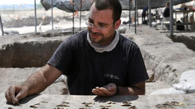 شاحر كريستين، خير العملات في سلطة الآثار الإسرائيلية، يحصي العملات الذهبية. (Yoli Schwartz, Israel Antiquities Authority)