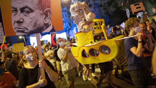 متظاهرون يرددون شعارات ويحملون لافتات خلال مظاهرة ضد رئيس الوزراء بنيامين نتنياهو خارج مقر إقامته في القدس، 1 أغسطس 2020. (AP Photo / Oded Balilty)