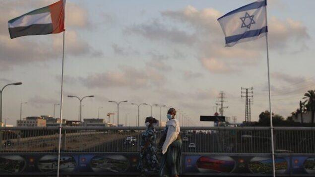 سيدتان ترتديا الكمامات للوقاية من جائحة كورونا تمران من أمام العلمين الإماراتي والإسرائيلي في 'جسر السلام' نتانيا، اغسطس، 2020.(AP Photo/Ariel Schalit)