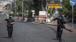 عناصر شرطة حماس يرتدون أقنعة وجه أثناء الحراسة في أحد شوارع مدينة غزة خلال إغلاق لمدة 48 ساعة بعد اكتشاف أول حالات إصابة بفيروس كورونا في القطاع، 25 أغسطس 2020 (AP / Khalil Hamra)