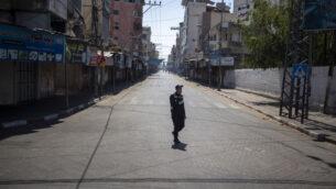 شرطي فلسطيني من حماس يرتدي قناعا للوجه أثناء الحراسة في أحد شوارع مدينة غزة خلال إغلاق لمدة 48 ساعة بعد اكتشاف أول حالات إصابة بفيروس كورونا في القطاع، 25 أغسطس 2020 (AP / Khalil Hamra)