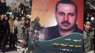 فلسطينيون يحملون صورة محمود المبحوح بينما يحمل آخرون نعشه، يسار، خلال جنازته في مخيم اليرموك، بالقرب من دمشق، سوريا، 29 يناير 2010 (AP Photo / Bassem Tellawi / File)