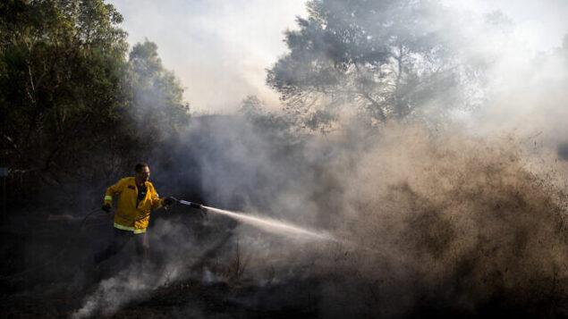 رجل اطفاء يحاول اخماد حريق ناجم عن بالونات حارقة تم إطلاقها من قطاع غزة، في كيبوتس كفار عزة على الحدود مع غزة ، 24 اغسطس 2020. (AP / Ariel Schalit)
