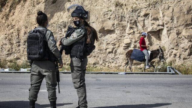 توضيحية: شرطيتان في شرطة حرس الحدود تحرسان حاجزا في الضفة الغربية، 22 أبريل، 2020. (Olivier Fitoussi/FLASH90)