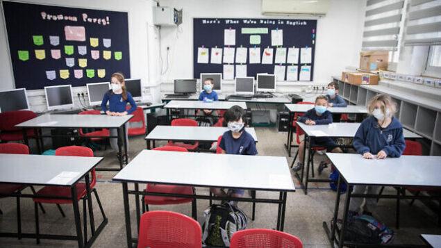 طلاب إسرائيليون يرتدون أقنعة واقية بعد عودتهم إلى المدرسة لأول مرة منذ تفشي فيروس كورونا، في 3 مايو، 2020، في القدس. (Olivier Fitoussi / Flash90)
