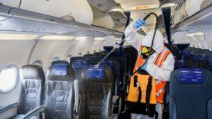 عامل يرتدي ملابس واقية يعقم طائرة إسرائيلية بعد وصولها من موسكو إلى مطار بن غوريون الدولي، 5 مايو 2020 (Yossi Zeliger / Flash90)