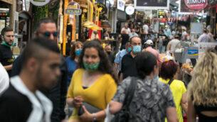إسرائيليون يتسوقون في سوق محانيه يهودا في القدس، 3 يونيو 2020. (Olivier Fitoussi / Flash90)