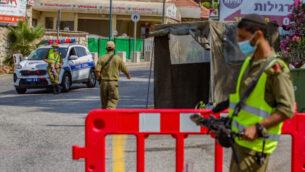 جنود إسرائيليون يحرسون عند حاجز في الجليل الأعلى في شمال إسرائيل، 27 يوليو 2020 (Flash90)