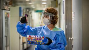 عاملة مختبر تجري اختبارا تشخيصيا لفيروس كورونا في مختبر في مستشفى إيخيلوف بمدينة تل أبيب، 3 أغسطس، 2020. (Yossi Aloni/Flash90)el)