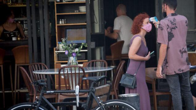 فحص درجة حرارة امرأة في تل أبيب، 4 أغسطس، 2020. (Miriam Alster/Flash90)