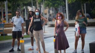 إسرائيليون يرتدون أقنعة واقية في تل أبيب، 4 أغسطس، 2020. (Miriam Alster / Flash90)