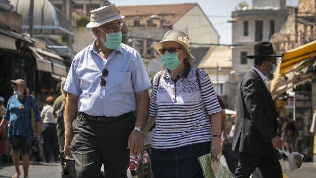 إسرائيليون يرتدون أقنعة الوجه للوقاية من فيروس كورونا، يتسوقون في سوق محانيه يهودا في القدس، 4 أغسطس، 2020. (Olivier Fitoussi / Flash90)