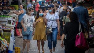 إسرائيليون يرتدون أقنعة واقية للوجه أثناء تسوقهم لشراء الطعام في سوق الكرمل في تل أبيب، 5 أغسطس، 2020. (Miriam Alster / FLASh90)