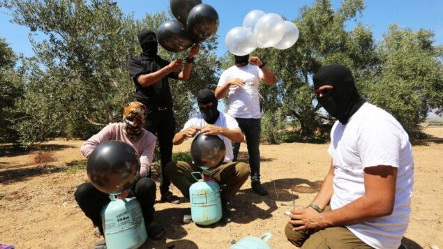 فلسطينيون يعدون بالونات حارقة لإطلاقها جوا باتجاه اسرائيل، بالقرب من الحدود بين اسرائيل وغزة، في الجزء الشرقي من القطاع، 10 اغسطس 2020 (Abed Rahim Khatib / Flash90)
