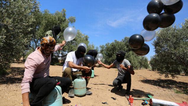 فلسطينيون يستعدون لإطلاق بالونات باتجاه إسرائيل، بالقرب من الحدود بين إسرائيل وغزة، في الجزء الشرقي من قطاع غزة، 10 أغسطس، 2020. (Abed Rahim Khatib / Flash90)