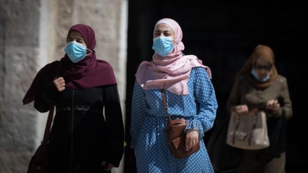 اشخاص يسيرون مع أقنعة وجه عند باب العامود، في البلدة القديمة في القدس، 17 أغسطس 2020 (Yonatan Sindel / Flash90)