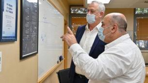وزير الدفاع بيني غانتس، يسار، يتحدث مع مدير معهد البحوث البيولوجية، البروفيسور شموئيل شابيرا، في المختبر في نس تسيونا، 6 أغسطس 2020. (Ariel Hermoni/Defense Ministry)