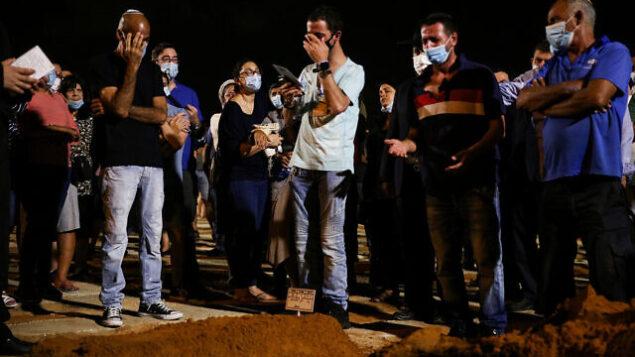 أقارب وأصدقاء يشاركون في جنازة ضحية الطعن الحاخام شاي أوحايون في مقبرة 'سيغولا' في بيتح تيكفا، 27 أغسطس، 2020. (Noam Revkin Fenton / Flash90)