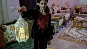 طفلة أفراد عائلة أبو صبيح بالقدس تحمل رفع فانوس في غرفة المعيشة في صورة لها قبل هدم منزل العائلة. (إياد أب صبيح)