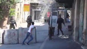 لقطة من مقطع فيديو يظهر شابا فلسطينيا يرشق الحجارة على جنود الجيش الإسرائيلي في الخليل من مسافة قصيرة، 29 أغسطس 2020 (video screenshot)