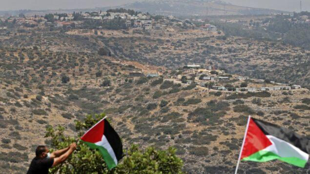 صورة توضيحية: متظاهرون فلسطينيون يلوحون بالاعلام خلال مظاهرة في بلدة بديا بالضفة الغربية، 6 يوليو 2020 (JAAFAR ASHTIYEH / AFP)