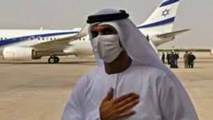 مسؤول إماراتي يقف بالقرب من طائرة تابعة لشركة 'ال عال' التي كانت تقل وفدا أميركيا إسرائيليا إلى الإمارات بعد الإعلان عن اتفاق التطبيع بين البلدين، فور وصولها إلى مطار أبوظبي، في أول رحلة طيران مباشرة من إسرائيل إلى الإمارات،  31 أغسطس، 2020.