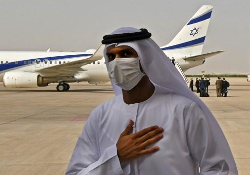 مسؤول إماراتي يقف بالقرب من طائرة شركة 'إل عال'، التي تقل وفداً أميركياً إسرائيلياً إلى الإمارات بعد اتفاق تطبيع، وهبطت على مدرج مطار أبوظبي، في أول رحلة تجارية على الإطلاق من إسرائيل إلى الإمارات. (Karim SAHIB / AFP)