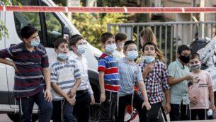 أطفال يرتدون أقنعة بسبب جائحة فيروس كورونا، يقفون في شارع بمدينة بني براك اليهودية المتشددة، 6 سبتمبر 2020 (JACK GUEZ / AFP)