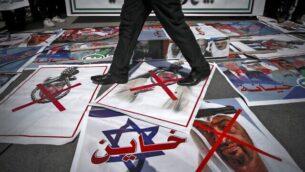 متظاهر يسير على صور موضوعة على الأرض لملك البحرين حمد بن عيسى آل خليفة وولي عهد أبوظبي الشيخ محمد بن زايد آل نهيان، خلال مظاهرة احتجاجية ضد قرار الإمارات العربية المتحدة والبحرين تطبيع العلاقات مع اسرائيل، في مدينة غزة، 15 سبتمبر، 2020. (Mohammed ABED / AFP)