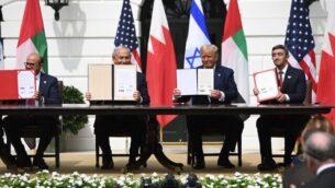 (من اليسار إلى اليمين) وزير الخارجية البحريني عبد اللطيف الزياني، ورئيس الوزراء الإسرائيلي بنيامين نتنياهو، والرئيس الأمريكي دونالد ترامب، ووزير الخارجية الإماراتي عبد الله بن زايد آل نهيان يرفعون الوثائق أثناء مشاركتهم في توقيع 'اتفاقية إبراهيم' التي تعترف من خلاله البحرين والإمارات العربية المتحدة تعترف بإسرائيل ، في البيت الأبيض في واشنطن العاصمة، 15 سبتمبر، 2020. (SAUL LOEB / AFP)