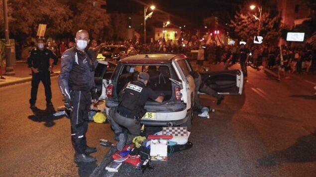 عناصر من الشرطة يفتشون سيارة رجل اندفع باتجاه الشرطة والمتظاهرين خلال مظاهرة ضد رئيس الوزراء بنيامين نتنياهو، خارج مقر إقامته الرسمي في القدس، 20 سبتمبر 2020 (Ahmad GHARABLI / AFP)