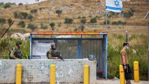 نود إسرائيليون يحرسون محطة حافلات عند مفرق تبواح بالقرب من مدينة نابلس في الضفة الغربية، 30 يونيو، 2020. (AP / Oded Balilty)