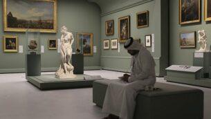 رجل إماراتي يجلس بالقرب من تمثال 'باثر'، الذي يُطلق عليه أيضا اسم 'فينوس' للنحات الفرنسي كريستوف غابرييل أليغرين، 1710-1795، في متحف اللوفر أبو ظبي، الإمارات العربية المتحدة، 19 ديسمبر، 2017.(AP Photo/Kamran Jebreili)