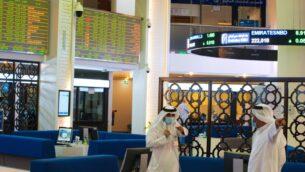 مواطنان إماراتيان، يرتديان أقنعة الوجه بسبب جائحة فيروس كورونا، يتحدثان على أرضية سوق دبي المالي في دبي، الإمارات العربية المتحدة، 7 يوليو 2020 (AP Photo / Jon Gambrell)