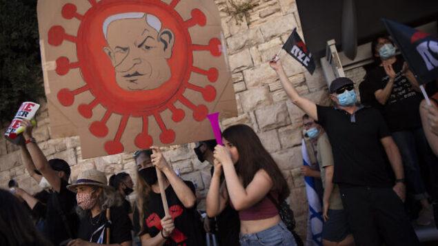 متظاهر يرفع رُسم عليها صورة رئيس الوزراء بنيامين نتنياهو خلال مظاهرة أ ضده خارج منزله في القدس، 31 يوليو، 2020. (AP / Oded Balilty)