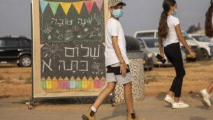 طلاب مدرسة ابتدائية يرتدون أقنعة وسط جائحة فيروس كورونا يمشون أمام لافتة كتب عليها 'عام جديد سعيد، مرحبا بالصف الأول' في اليوم الدراسي الأول في كفار يونا، 1 سبتمبر 2020 (AP Photo / Ariel Schalit)