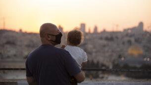 رجل يرتدي قناعا للوقاية من فيروس كورونا يحمل طفلا يراقب غروب الشمس خلف قبة الصخرة في جبل الزيتون بالقدس ، 2 سبتمبر ، 2020. (AP Photo / Maya Alleruzzo)
