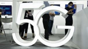 زوار يرتدون أقنعة للحماية من فيروس كورونا يمرون خلف لافتة 5G في معرض بكين الدولي للتكنولوجيا الفائقة في بكين، الصين، 17 سبتمبر 2020 (AP Photo / Ng Han Guan)