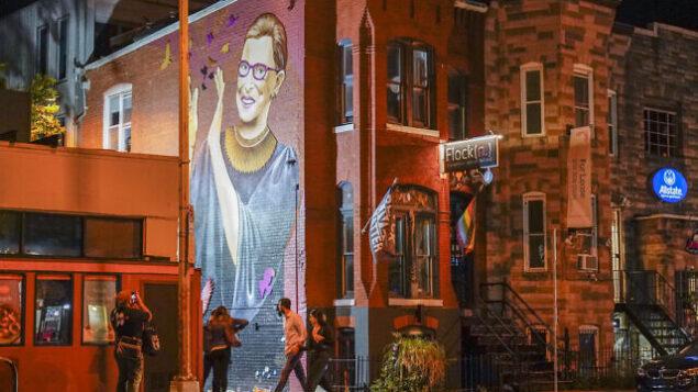 أشخاص يتجمعون تحت لوحة جدارية لقاضية المحكمة العليا روث بادر غينسبورغ في حي يو ستريت بواشنطن، 18 سبتمبر 2020، بعد الإعلان عن وفاة غينسبورغ بسرطان البنكرياس عن عمر يناهز 87 عامًا (AP Photo / Pablo Martinez Monsivais)