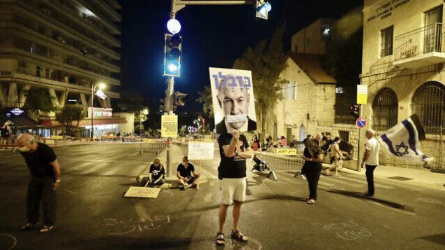 تظاهرون إسرائيليون يرفعون لافتات ويرددون شعارات خلال مظاهرة ضد رئيس الوزراء بنيامين نتنياهو بالقرب من مقر إقامة رئيس الوزراء في القدس، 20 سبتمبر، 2020. (AP Photo/Sebastian Scheiner)