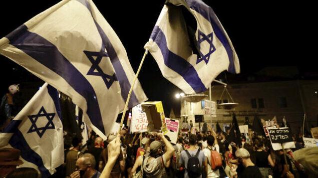 متظاهرون مناهضون لنتنياهو يلوحون بالأعلام ويحملون لافتات ويرددون الشعارات خلال مظاهرة خارج مقر إقامة رئيس الوزراء في القدس، 20 سبتمبر 2020 (AP Photo / Sebastian Scheiner)