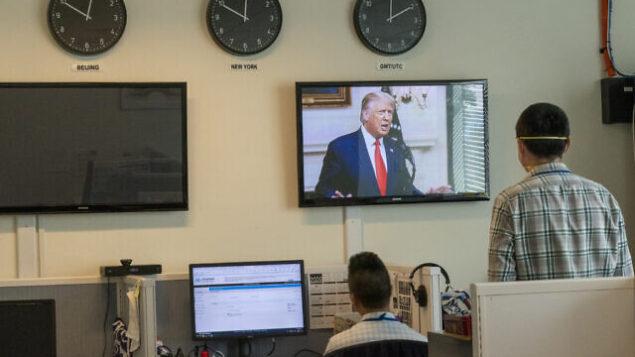 مراسلون في وكالة أنباء 'شينخوا' الصينية يشاهدون الرئيس الأمريكي دونالد ترامب على شاشة فيديو  وهو يلقي كلمة عن بعد أمام الدورة 75 للجمعية العامة للأمم المتحدة في 22 سبتمبر 2020، في مقر الأمم المتحدة.  (AP/Mary Altaffer)