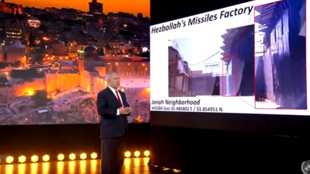 رئيس الوزراء بنيامين نتنياهو يعرض ما يقول إنه مدخل إلى مستودع أسلحة تابع ل'حزب الله' بجوار محطة وقود في حي جناح في بيروت، في خطاب بالفيديو أمام الجمعية العامة للأمم المتحدة، 29 سبتمبر، 2020. (UN screenshot)